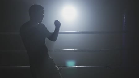 defending : Kickboxer training in low light ring. Silhouette on dark background. Sportsman boxing in smoky gym. Muay thai fighter punching in slow motion Stock Footage