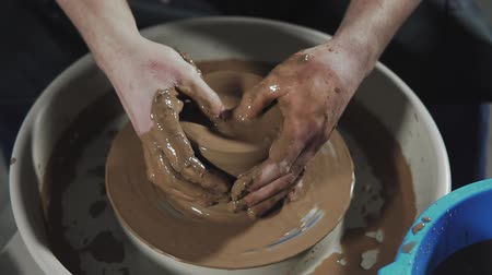 clay pot : Top view on potters hands work with clay. Potter shapes clay product with pottery tools. Potter shapes clay product with pottery tools on potters wheel Stock Footage
