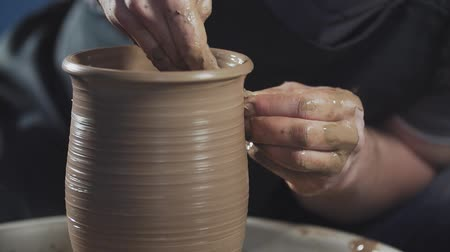 potter wheel : Hands gently create correctly shaped handmade from clay. Potter creates product on potters wheel or on potters lathe spinning pottery.