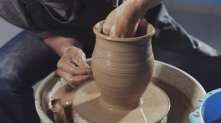 beeldhouwer : Potter creates product on potters lathe spinning pottery. Hands gently create correctly shaped handmade from clay in slow motion