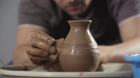 ware : Close up of Potter creates product on potters wheel or on potters lathe spinning pottery. Hands gently create correctly shaped handmade from clay