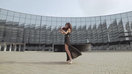 hegedűművész : Beautiful woman in black dress playing violin near glass building in slow motion. Urban art concept Stock mozgókép