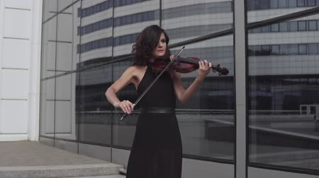 hegedűművész : Elegant violinist in black dress near glass building. Urban art concept. Stock mozgókép