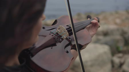 hegedűművész : Young violinist in long black dress plays with inspiration at sea background. Beautiful girl with violin. Close up of violin. Art concept in 4k