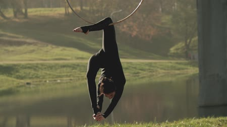 гимнастика : Female doing some acrobatic elements on aerial hoop outdoors. Air gymnastics woman performs acrobatics tricks on aerial hoop. Flexible brunette hanging in ring for aerial acrobatics in slow motion Стоковые видеозаписи