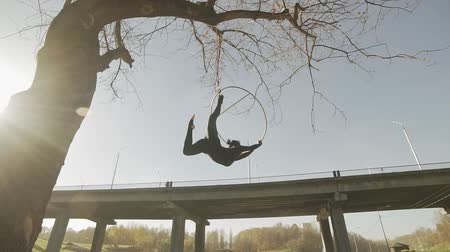 abroncs : Air gymnastics brunette performs acrobatics tricks on aerial hoop. Silhouette of woman doing some acrobatic elements on aerial hoop outdoors. Flexible woman hanging in ring for aerial acrobatics