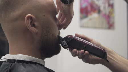 beard trim : Close up of male barber trimming beard with shaver. Professional shaving bearded man in slow motion. Barber shaving beard with electric razor and comb in male salon.