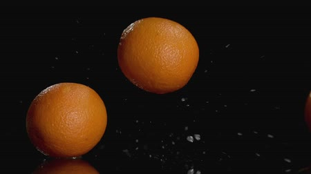 rind : Slo-motion of oranges falling on dark background with copy space at the top.