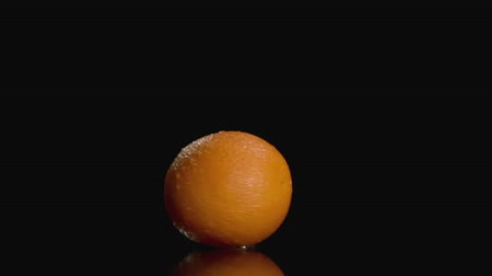 rind : Slo-motion orange twisting on dark background at center with copy space.