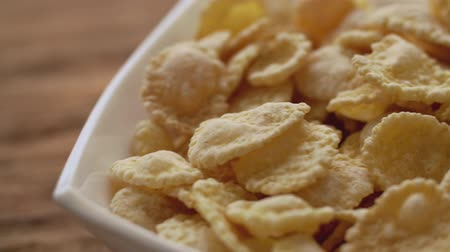pehely : Corn flakes in white bowl in close up. Slide right. Stock mozgókép