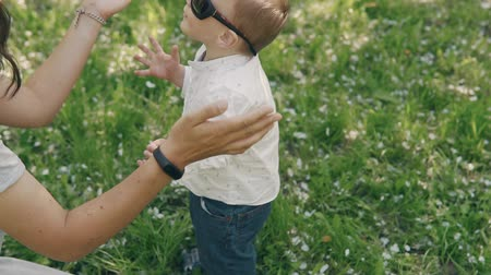przytulanie : Brunette young mother and little son playing with sunglasses outdoors. Mom showing love and affection to son. Motherhood concept in slow motion Wideo