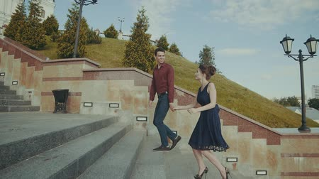 parte : Lovely couple walking upstairs to the left. Smiling male and female moving outdoors. Wide stabilized angle Stock Footage