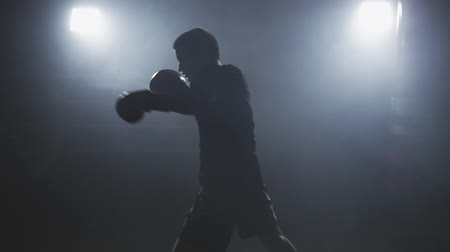 tiro do estúdio : Kickboxer training in smoky studio. Muay thai fighter punching. Silhouette on dark background