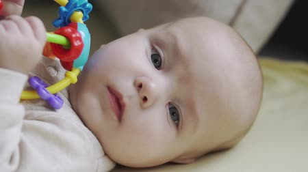 閉じる : Little baby boy lying on bed and looking at camera. Concept of caring for children and parental love. 動画素材