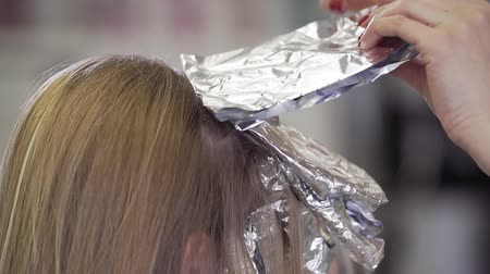 bleekwater : Stylist kapper maakt haarkleuring, blond. Haarstylist die haarkleurstof aanbrengt om de haarkleur te verlichten. Close-up weergave in slow motion Stockvideo