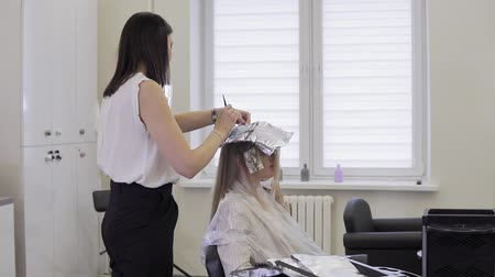 vlasy : Hairdresser makes hair coloring. Close up of Hair stylist applying hair coloring dye to lighten up hair tone in slow motion.