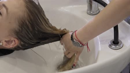 mycie rąk : Beautiful girl washes her hair before haircut in beauty salon. Close up of Hair washing at hairdressing. Washing blonde woman in beauty salon