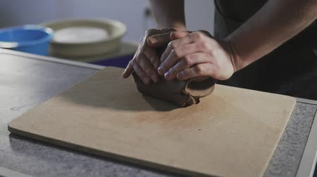 фасонный : Close up of Potter hands kneads clay in slow motion. Hands gently create correctly shaped handmade from clay. Handmade
