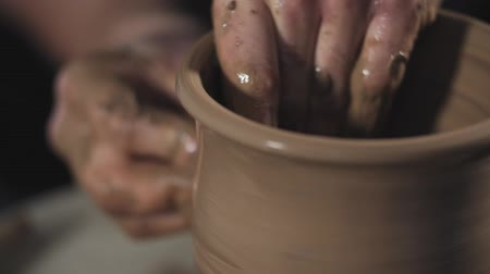 ware : Man works with potters wheel and clay. Processing clay ware. Ceramics of handwork and clay ware on potters wheel. Close up view of hands