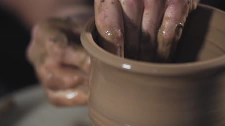 глина : Hands gently create correctly shaped handmade from clay. Potter creates product on potters wheel or on potters lathe spinning pottery.