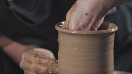 esculpir : Close up of potter working with clay on potters wheel. Man gently create jug from clay in slow motion. Vídeos