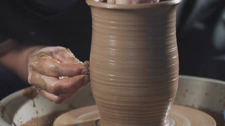 esculpir : Potter creates product on potters lathe spinning pottery. Hands gently create correctly shaped handmade from clay in slow motion