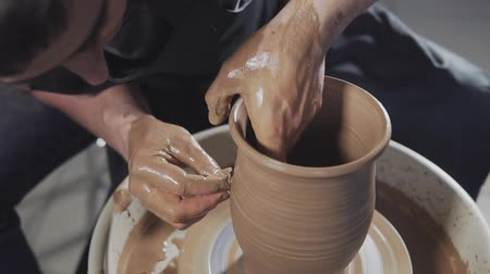esculpir : Man creates product on potters wheel or on potters lathe spinning pottery. Hands gently create jug from clay. Handmade. Craft.