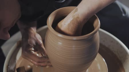 moldagem : Hands gently create correctly shaped handmade from clay. Potter creates product on potters wheel or on potters lathe spinning pottery