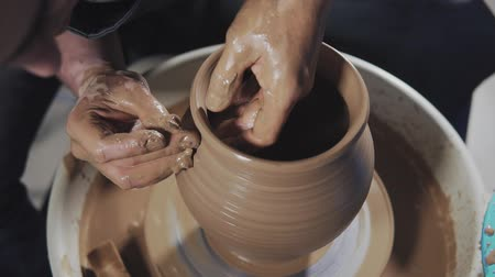 молдинг : Potter creates product on potters lathe spinning pottery. Close-up of Hands gently create correctly shaped handmade from clay in slow motion