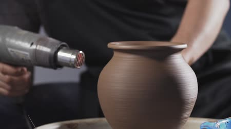 potter wheel : Potter dry clay jug with dryer. Man hands making clay jug. Handmade. Craft. Close up in slow motion Stock Footage