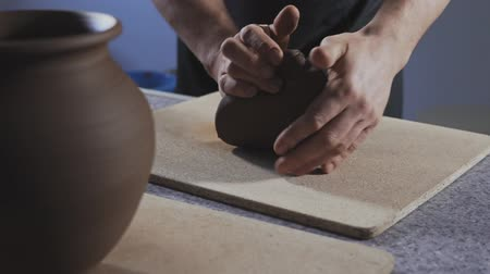 kneads : Close up of Potter kneads the clay in slow motion. Hands gently create correctly shaped handmade from clay