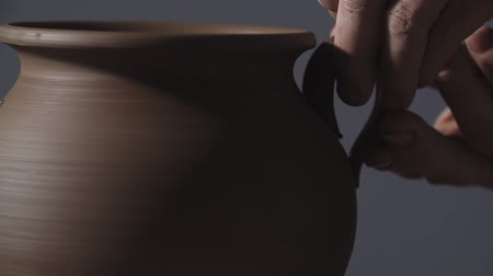 oleiro : Potter make jug handle from clay in slow motion. Close up of potters work. Man hands making clay product