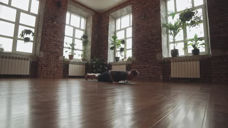 規律 : Man practice yoga pose in studio with brick wall. Attractive man making yoga pose in gym in slow motion. Fitness and healthy lifestyle concept with copyspace