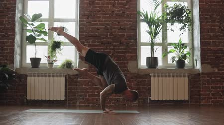 disciplina : Young man doing asana. Hand standing pose. Yogi master workout in urban studio. Guy doing yoga indoors near windows. Healthy lifestyle concept Stock Footage