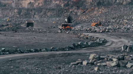 pedreira : Heavy trucks carry the stone in the quarry mining granite