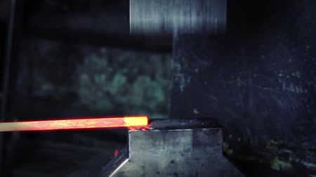 olvad : blacksmith working with hot glowing metal, bending steel in a smithery