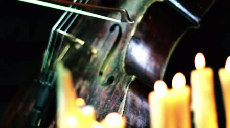 houslista : old wooden cello playing in a candles light - camera moving on a dolly Dostupné videozáznamy