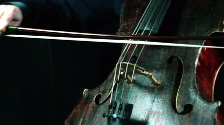 instrumentos : Old cello playing on a black background closeup
