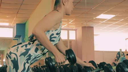 Athletic young woman working out on a fitness exercise equipment at the gym. Health, sport and workout concept - 4K stock footage video