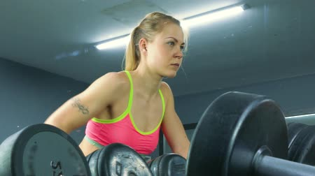 melegítőben : Athletic young woman working out on a fitness exercise equipment at the gym. Health, sport and workout concept - 4K stock footage video