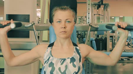 dres : Athletic young woman working out on a fitness exercise equipment at the gym. Health, sport and workout concept - 4K stock footage video