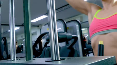 flexão : Athletic young woman working out on a fitness exercise equipment at the gym. Health, sport and workout concept - 4K stock footage video