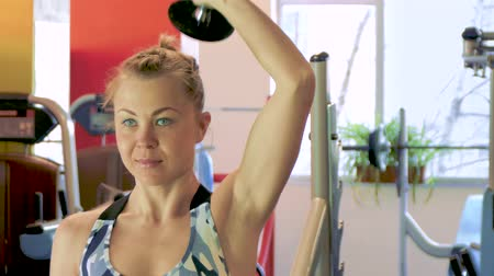 dupa : Athletic young woman working out on a fitness exercise equipment at the gym. Health, sport and workout concept - 4K stock footage video