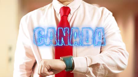 nomeação : Canada. Businessman chooses country on hologram clock on light background. Concept: business trip,hologram, technology, augmented reality, future, travel 4k footage clip