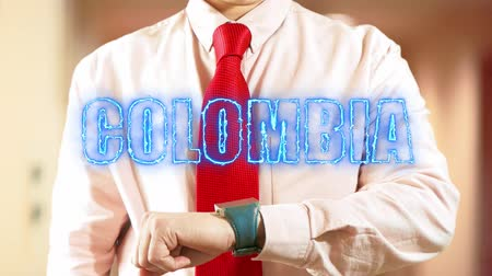 widgets : Colombia.Businessman chooses country on hologram clock on light background. Visual screen. Futuristic Interface 4k footage clip Stock Footage