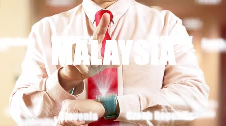 nomeação : Malaysia. Businessman operating a smart device chooses а country in light office. Concept: business trip,hologram, technology, augmented reality, future, travel 4k footage clip