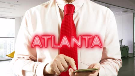 ATLANTA  Businessman operating a smart device chooses �° city on light background. Concept: business trip,hologram, technology, augmented reality, future, travel 4k footage clip Stock Footage