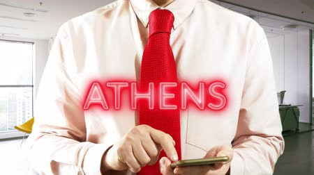 nomeação : ATHENS  Businessman operating a smart device chooses Ã�° city on light background. Concept: business trip,hologram, technology, augmented reality, future, travel 4k footage clip