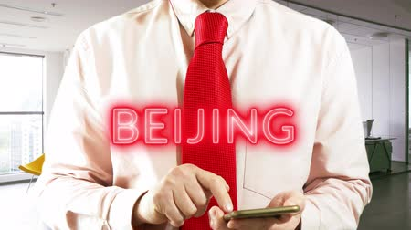 BELJING  Businessman operating a smart device chooses �° city on light background. Concept: business trip,hologram, technology, augmented reality, future, travel 4k footage clip