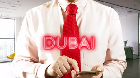 DUBAI Businessman operating a smart device chooses �° city on light background. Concept: business trip,hologram, technology, augmented reality, future, travel 4k footage clip Stock Footage
